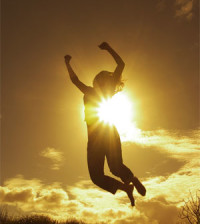 woman jumping with sun behind her