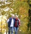 mature couple walking in park in fall